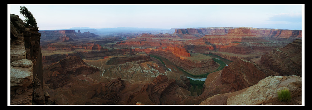 Dead  Horse Point in Canyonlands: a composite of 20 images shot at dawn. If  you look at the bottom part of the image, you will notice that you are  looking straight down on the road below. A friend of mine, Doug, held me by the belt as I leaned over my tripod to shoot vertically downward. My life was literally in his hands.