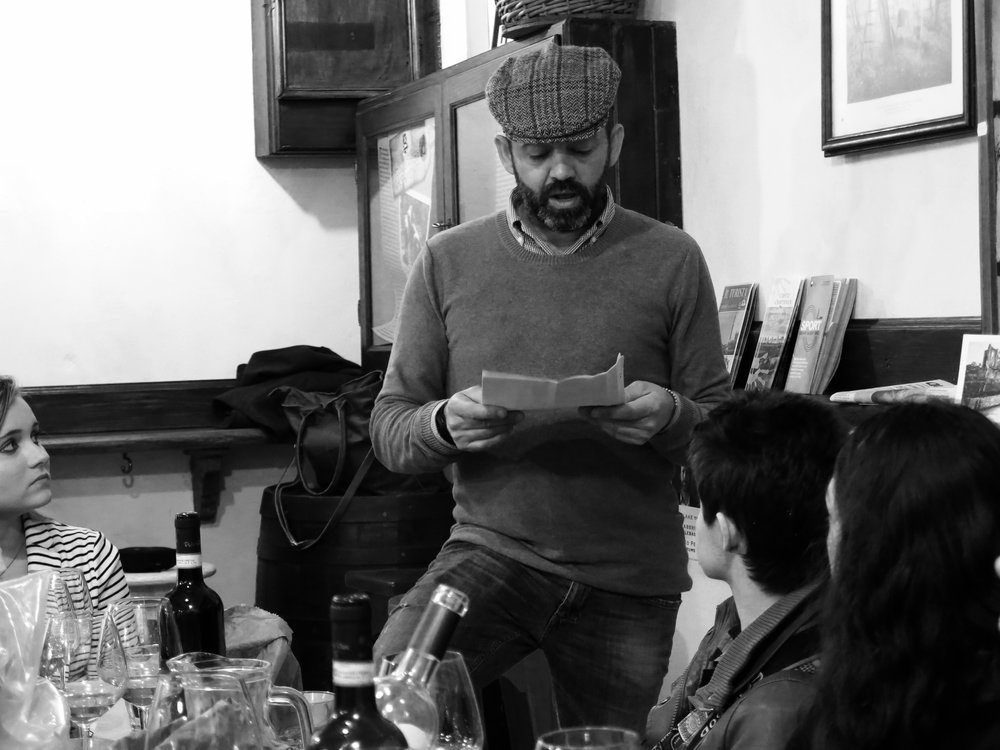 Emanuele, owner of Pretto Prosciutteria in Siena, reading his grandfather's poetry to our guests as they finish a mid-afternoon refreshment of local delicacies from the Chianti.