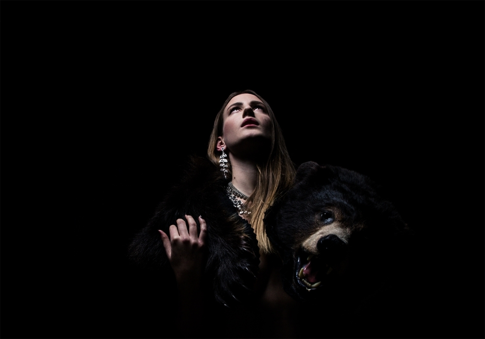 Beautiful woman with bear, in light and shadow