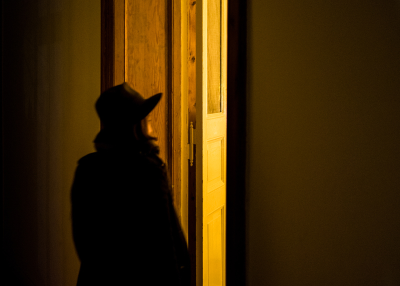 woman-with hat-walking-yellow-door-night