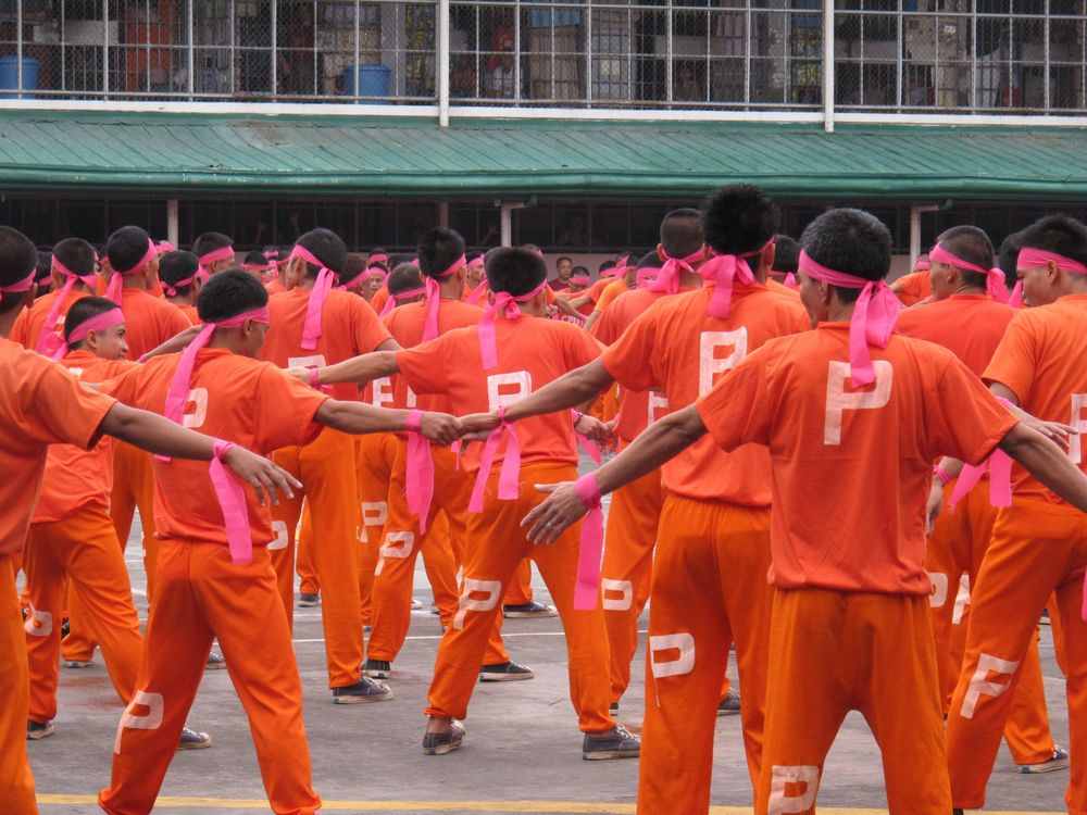 Inmate dancers wearing pink ribbons to indicate cancer fundraising efforts. Yes, the prison is raising funds for cancer research.