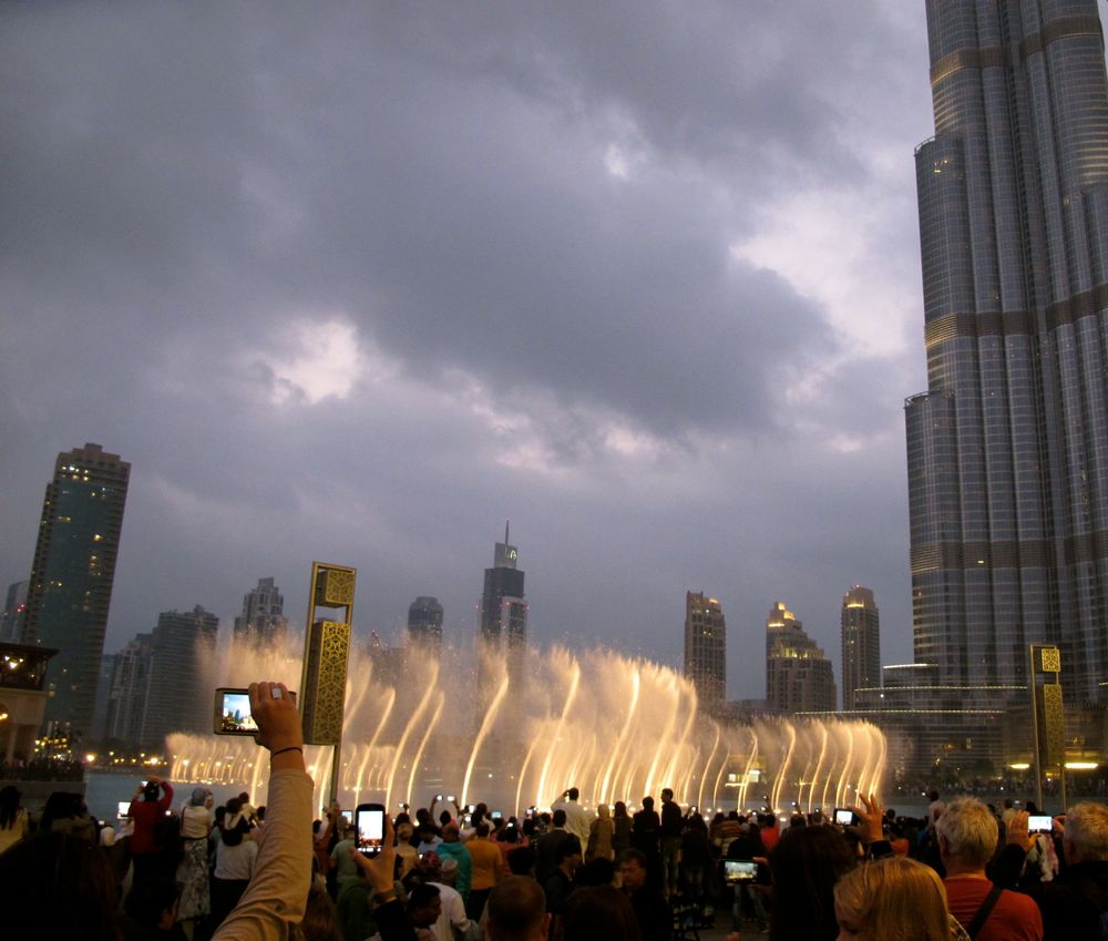 Clouds swirl above the dancing fountain at the Mall of Dubai.