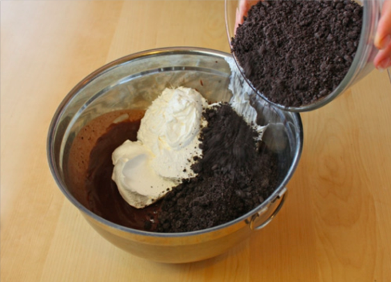 "Add the whipped topping and about half the ""dirt""."