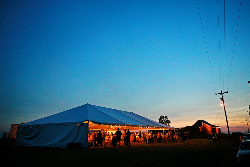 The reception marquee stands in a field next to Po' Monkey's juke joint (background) for John & Kate's wedding.