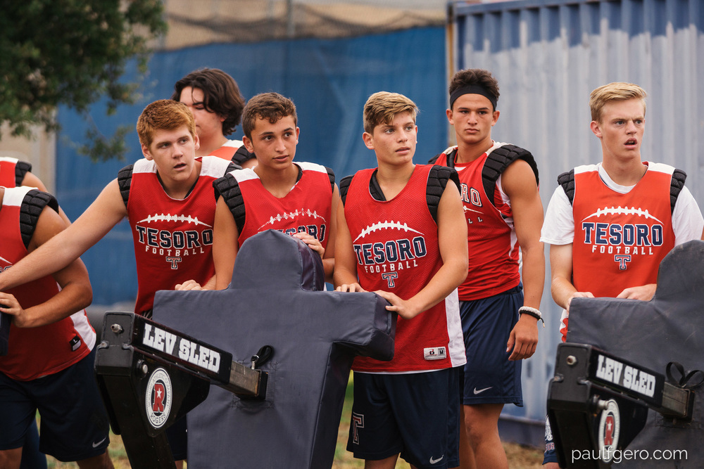 Tesoro players listen to their coach as they prepare to move the blocking sled during Day One of Fall Camp at the school on Monday.  122mm, 250 ISO, 1/50  0th at f2.8.