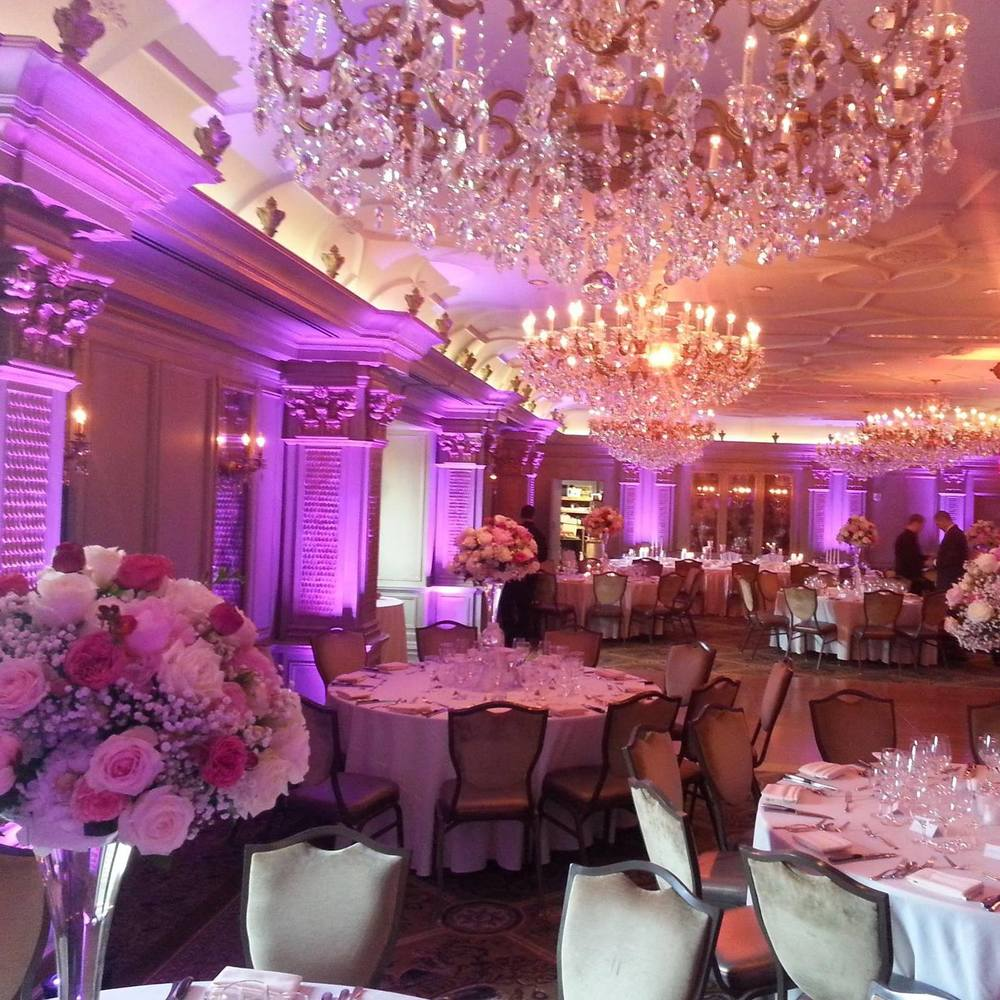 Pink uplighting, pinspots, and amber chandelier lighting inside the ballroom at the Grand Bohemian Hotel in Asheville