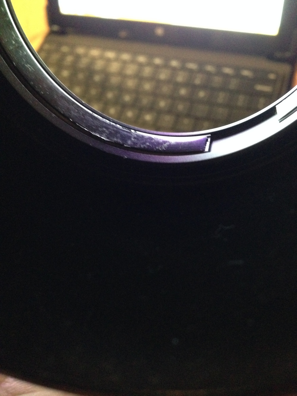 "Different light: see those ""scuff"" marks?  Those are actually glue residue. The glue would seep out from under those ""strips"" over time and onto the lens barrel. Pulling the hood on and off the barrel left extra residue back on top of the ""strips."""