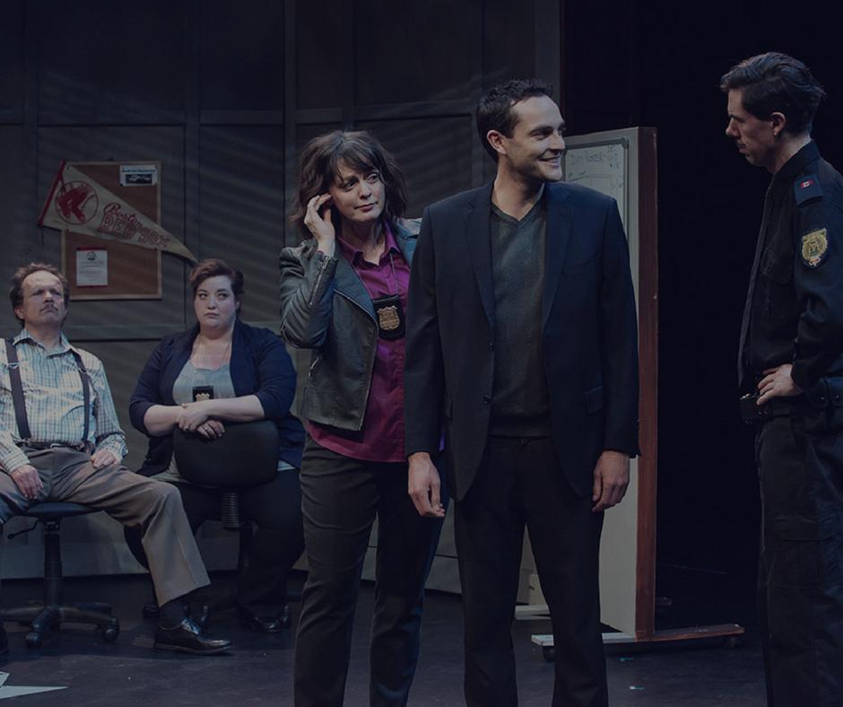 Image Description: In a photo from Undercover a smiling man faces a stern police officer. There is a detective standing behind him and two more detectives sitting behind in a moody police station.