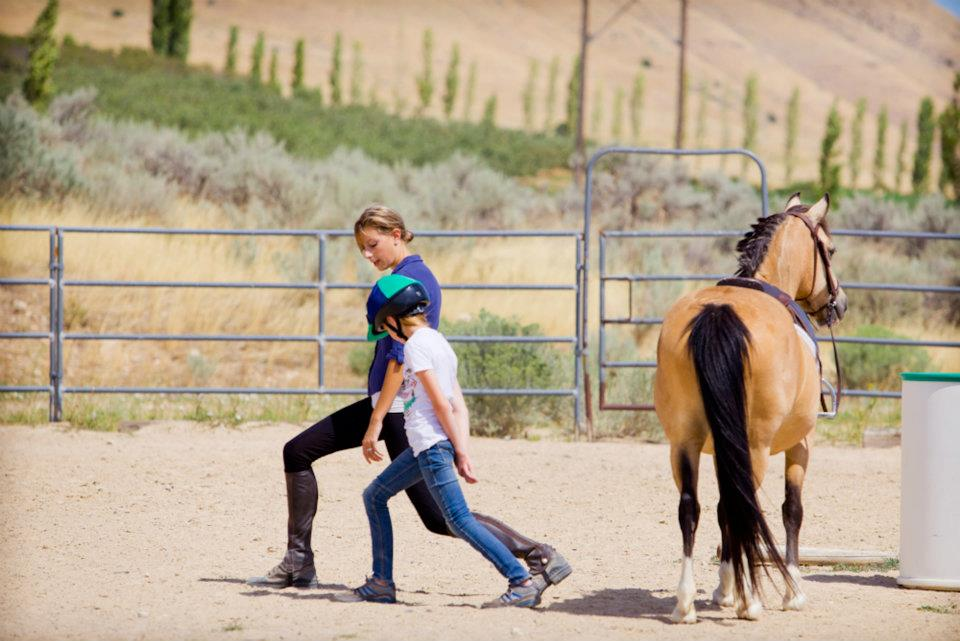 Kate teaches Rylie some stretches she can do at home to improve her riding while Buttercup looks on.