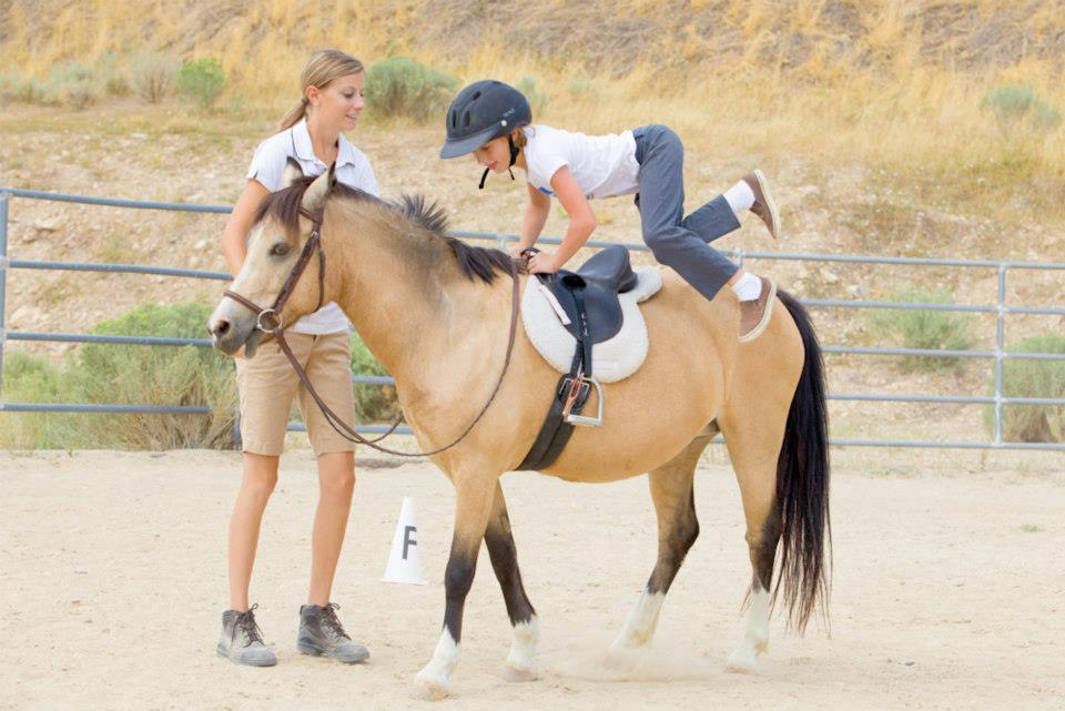 Kaycee practicing emergency dismount on Buttercup under the watchful eye of instructor Kate.