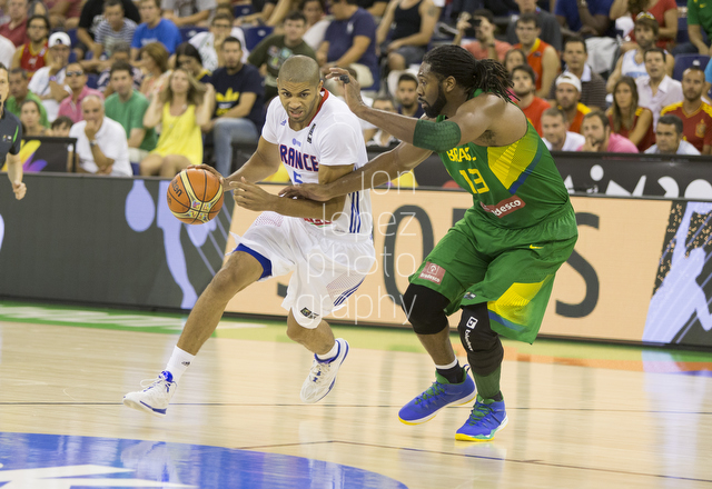 France's Nicolas Batum drives the lane on Brazil's Nene Hilario in Granada, Spain.