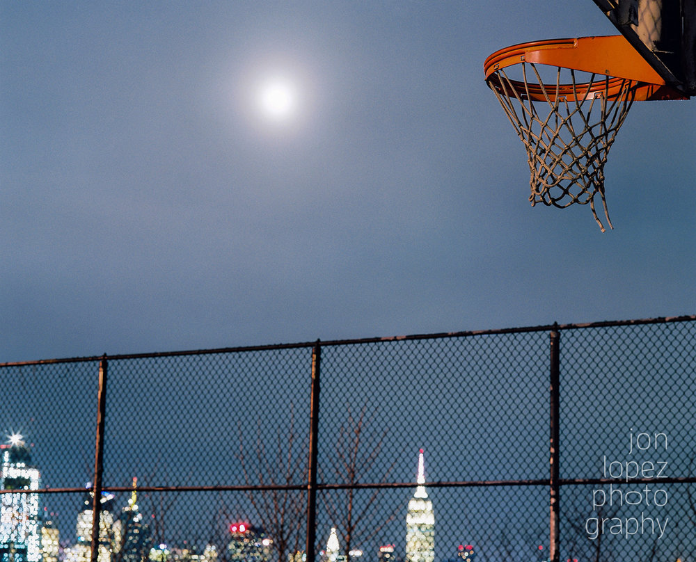 I tried to capture the moonrise over the NYC skyline but the overcast skies and the bright sun didn't allow for that, so I settled for this shot of the full (super) moon shining brighter than your average full moon and illuminating this basketball court at night. This photograph was taken on Fuji Pro 400h film using the Mamiya RB67. Photo credit: Jonathan Lopez