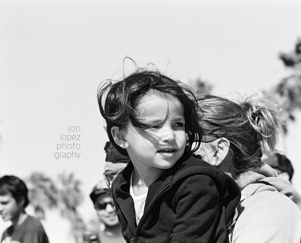 Young girl takes in the action at Venice Beach, shot on Kodak   Tri-X 400.