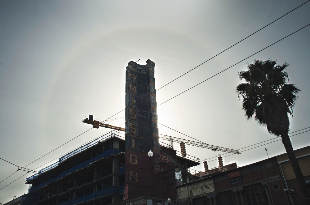 "I captured this photo to represent the rapid new development taking place in The Mission. The circular rainbow presented itself as I used the ""New Mission"" sign to block the sun from over exposing my photo. I felt the construction crane, dilapidated sign and palm tree were all symbolic in representing of what is happening in this small part of the city, quite possibly all over America. In this moment everything was speaking to me."
