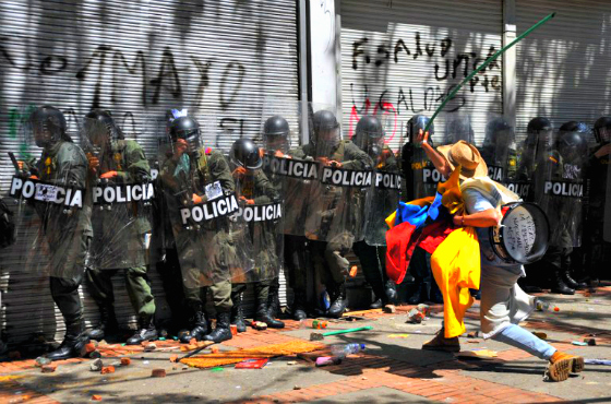 A protester attacks riot police in Bogotá, August 2013