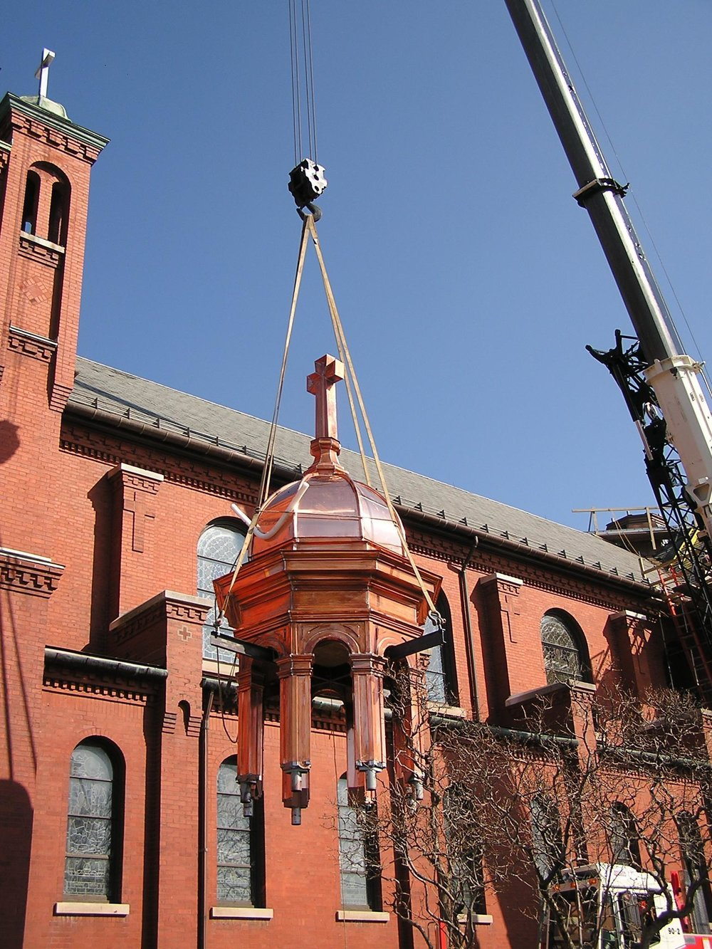 Workers with Leo J. Roth Corporation installing copper domes, these domes were fabricated in Leo J. Roth's Sheet Metal Fabrication Facility