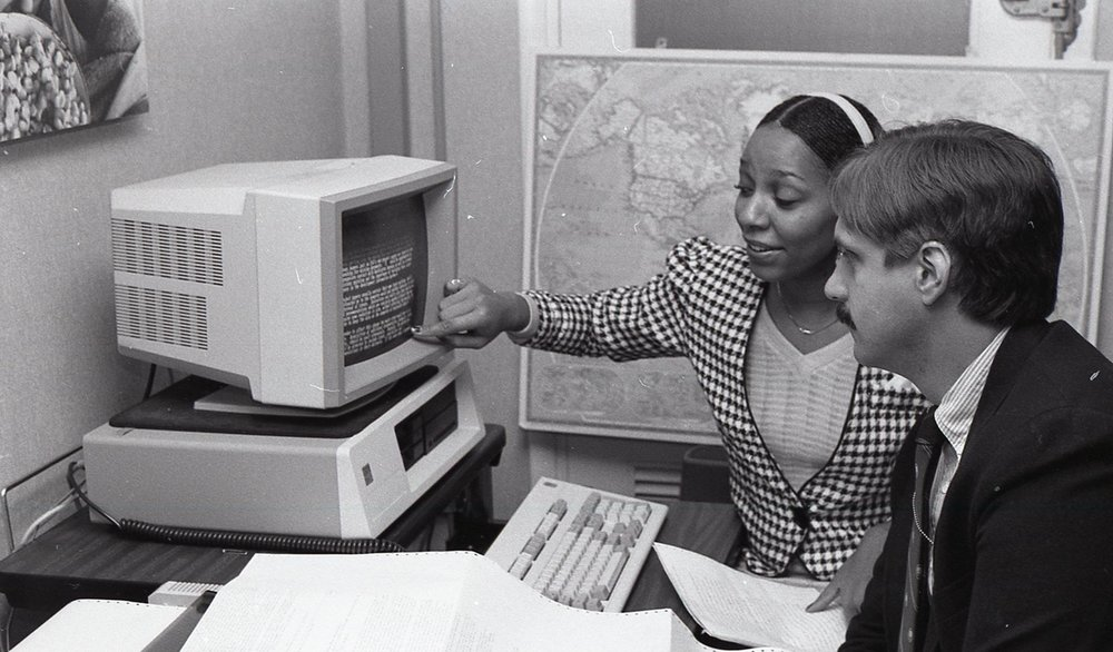 Two USAID employees working on a computer in 1988 (USAID)