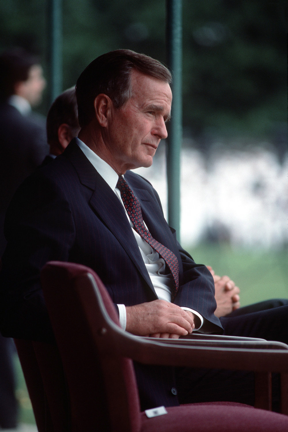 President George H.W. Bush listens to a speech during the retirement ceremony for Admiral William J. Crowe Jr., chairman, Joint Chiefs of Staff. The ceremony is being held at the US Naval Academy in Annapolis.