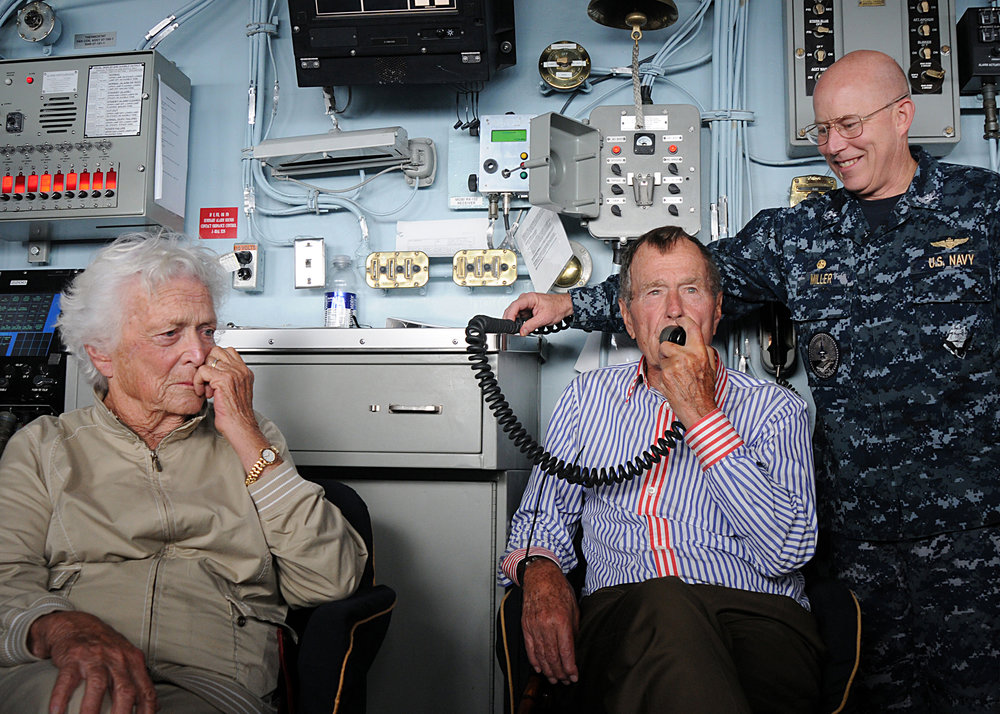 Former President George H.W. Bush speaks to sailors via the ship's announcing system aboard the aircraft carrier that bears his name, USS George H.W. Bush (CVN 77). Bush and his wife, Barbara, spent their time aboard watching flight operations, touring the ship and visiting with the crew. George H.W. Bush is conducting training in the Atlantic Ocean.