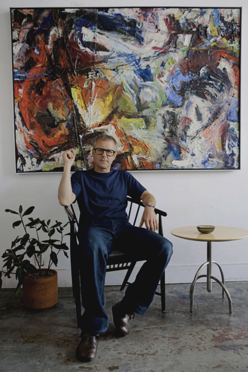 Proprietor Chris Houston holds court in a Sonna Rosen chair from 1948 in front of a Kyran Aviani oil painting.  Next to him is a 1993 Lawrence Laske Sagauro Cactus table.