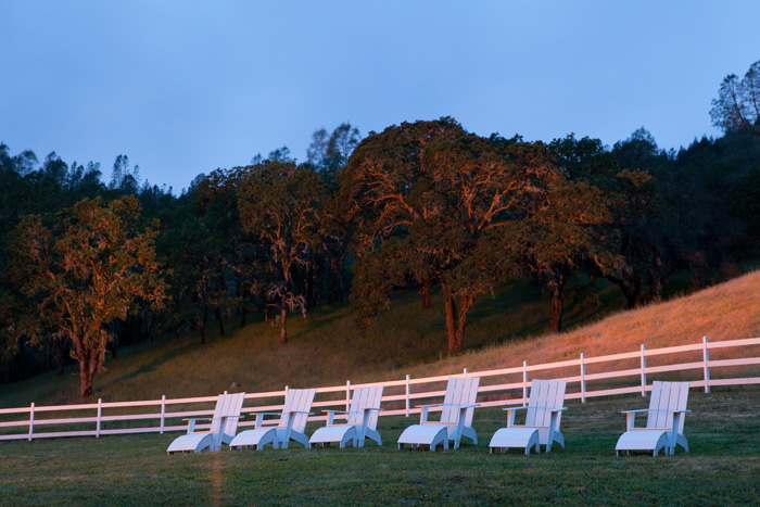 A few white lawn chairs and a simple white fence turn a seemingly plain field into something elegant and peaceful.