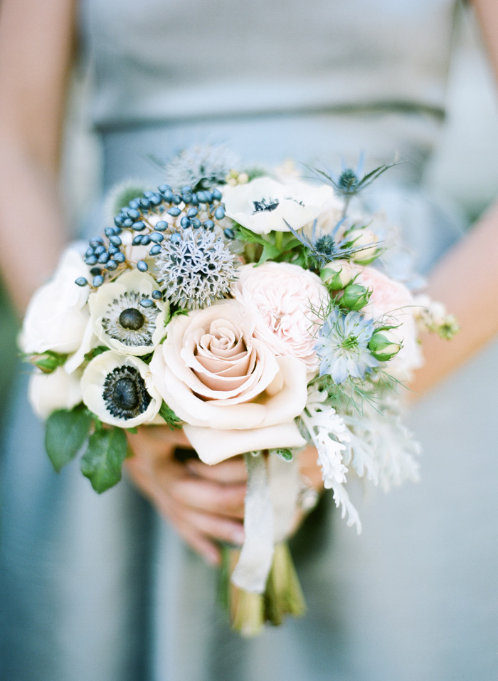 A bridesmaid's bouquet of white anemones, blush roses, and beautiful blue flowers.