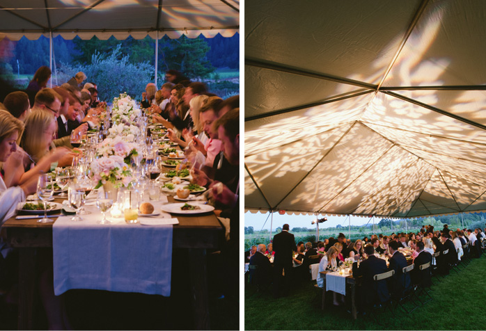 Guests enjoy dinner under a large white tent at the beautifully decorated long wooden tables.
