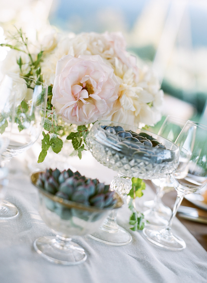 Little glass vases full of light pink roses and blue flowers decorated each table.