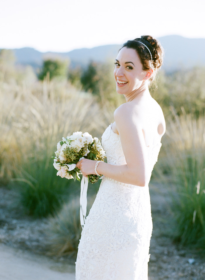 The bride wore a form-fitting, strapless, lace dress with simple pearl earrings and a matching pear bracelet.
