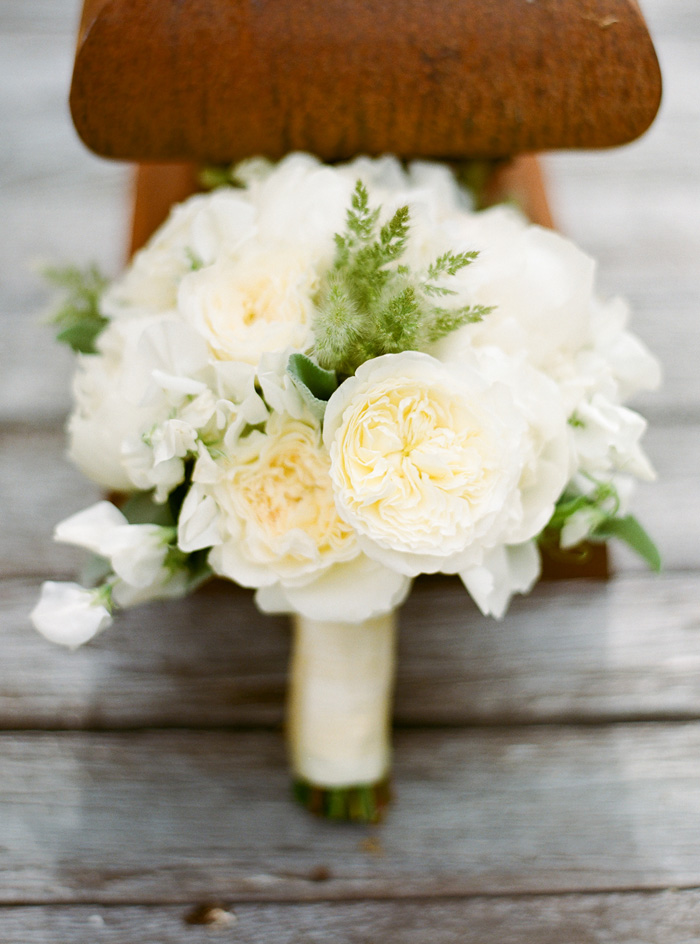 The bridal bouquet is simple, elegant, and classy, with an assortment of white peonies, roses, and green leaves.