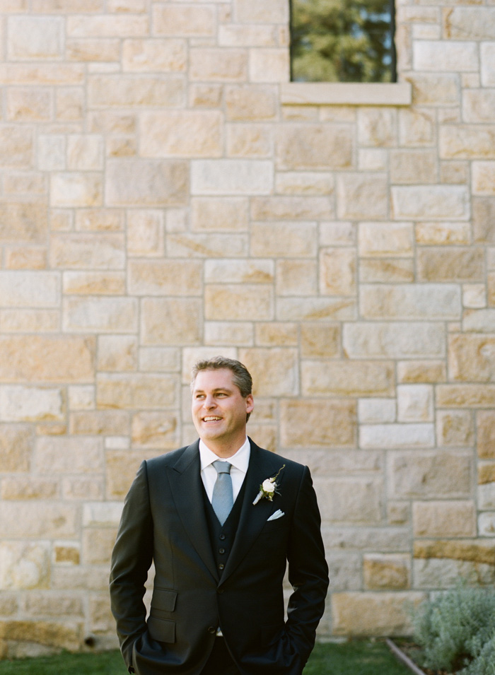 An excited groom awaits his bride in front of the tall church walls.