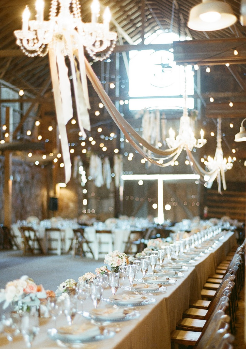sylvie-gil-film-photography-wedding-santa-margarita-ranch-long-wooden-table-chandelier-flowers