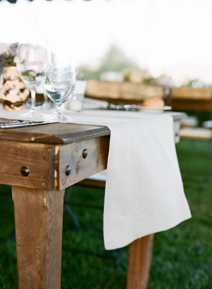 Long wooden tables with white table runners provided plenty of space for everyone attending the wedding.
