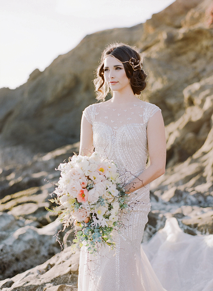 Bride in sheer sequined gown holds rustic pastel bouquet, stands on rocks by the California coast; Sylvie Gil Photography