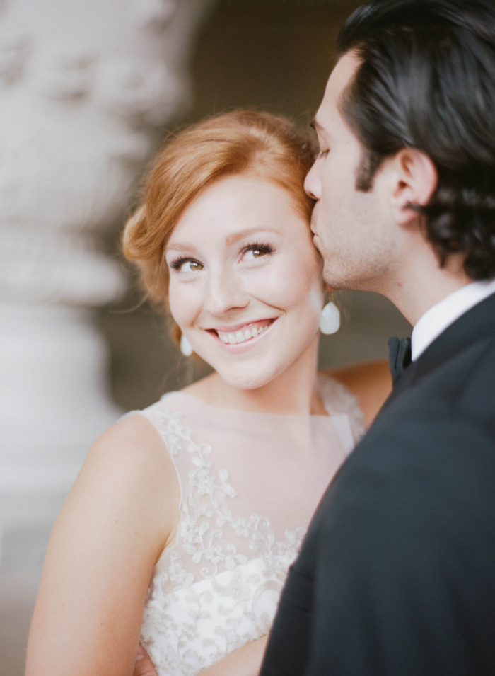 Groom kisses redhead bride in tulle and lace wedding gown; Sylvie Gil Photography
