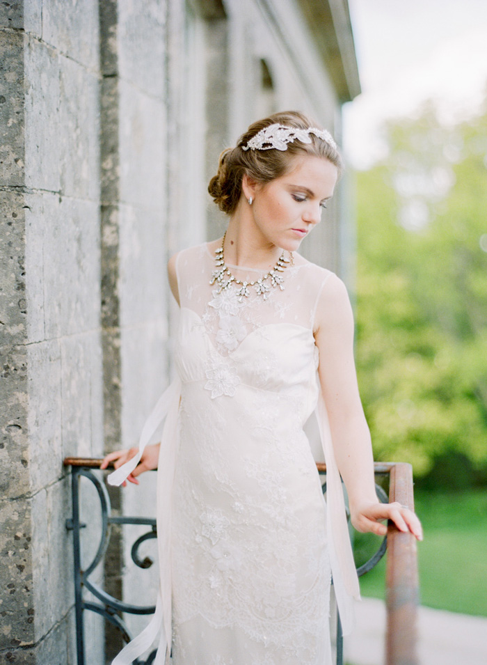 Bride on balcony of Normandy chateau with lace sweetheart neckline wedding gown; Sylvie Gil Photography