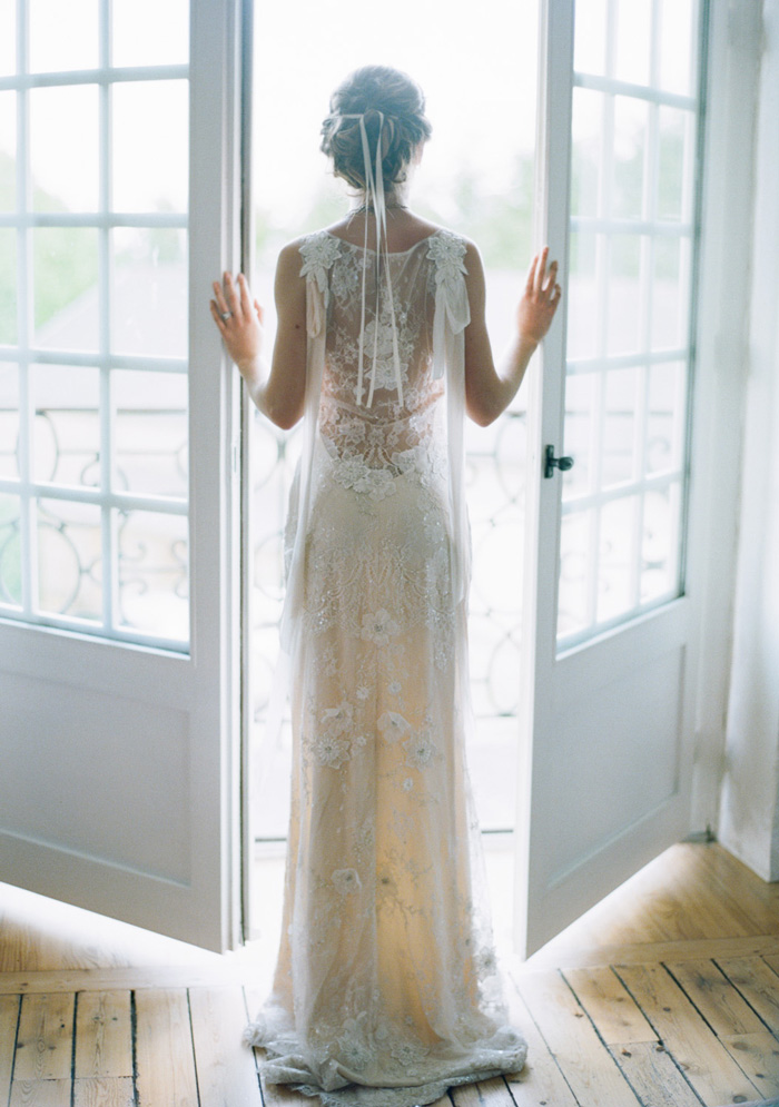 Bride in sheer lace gown stands at chateau balcony in Normandy;  Sylvie Gil Photography