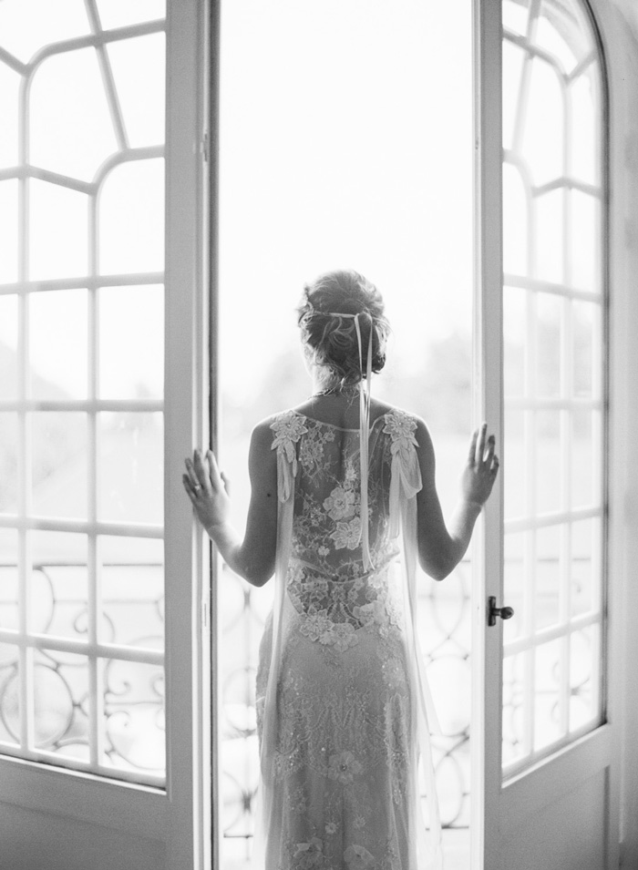Bride at balcony French doors in sheer lace wedding gown;  Sylvie Gil Photography