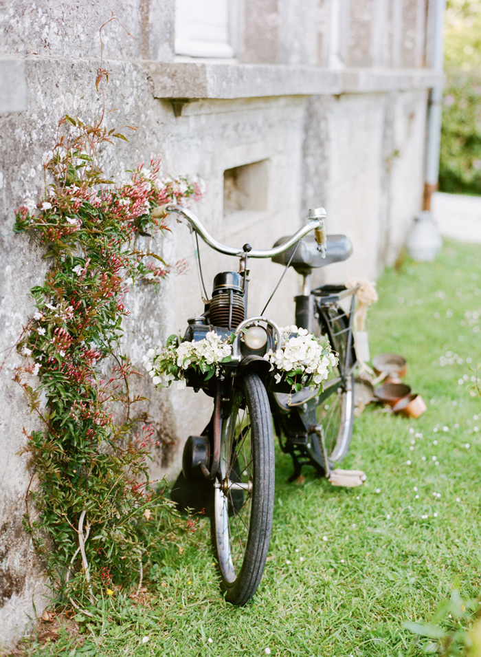 Vintage bicycle with floral decorations leans against Normandy chateau in France; Sylvie Gil Photography