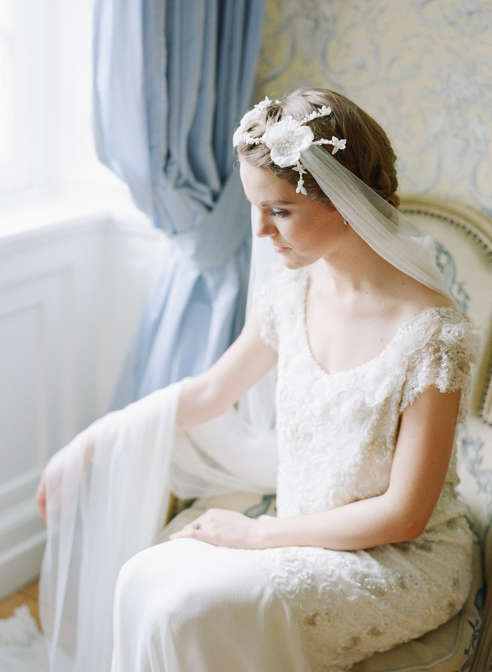 Bride with lace hairpiece veil sits in a vintage armchair in Normandy chateau in France;  Sylvie Gil Photography