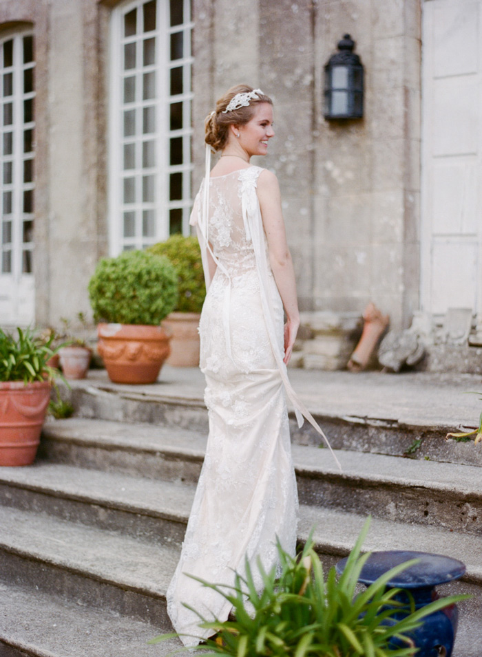 Bride climbs steps to Normandy chateau wearing gorgeous sheer lace wedding gown; Sylvie Gil Photography