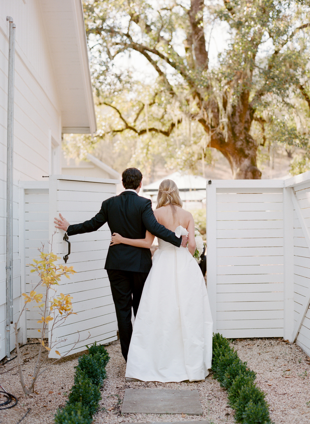 Bride and groom walk through gate arm in arm; Sylvie Gil Photography