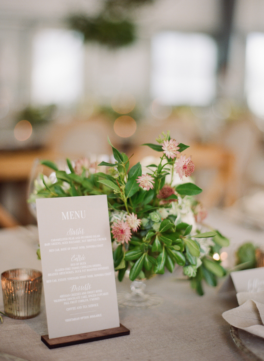 Menu card, votives and floral centerpiece at reception; Sylvie Gil Photography.