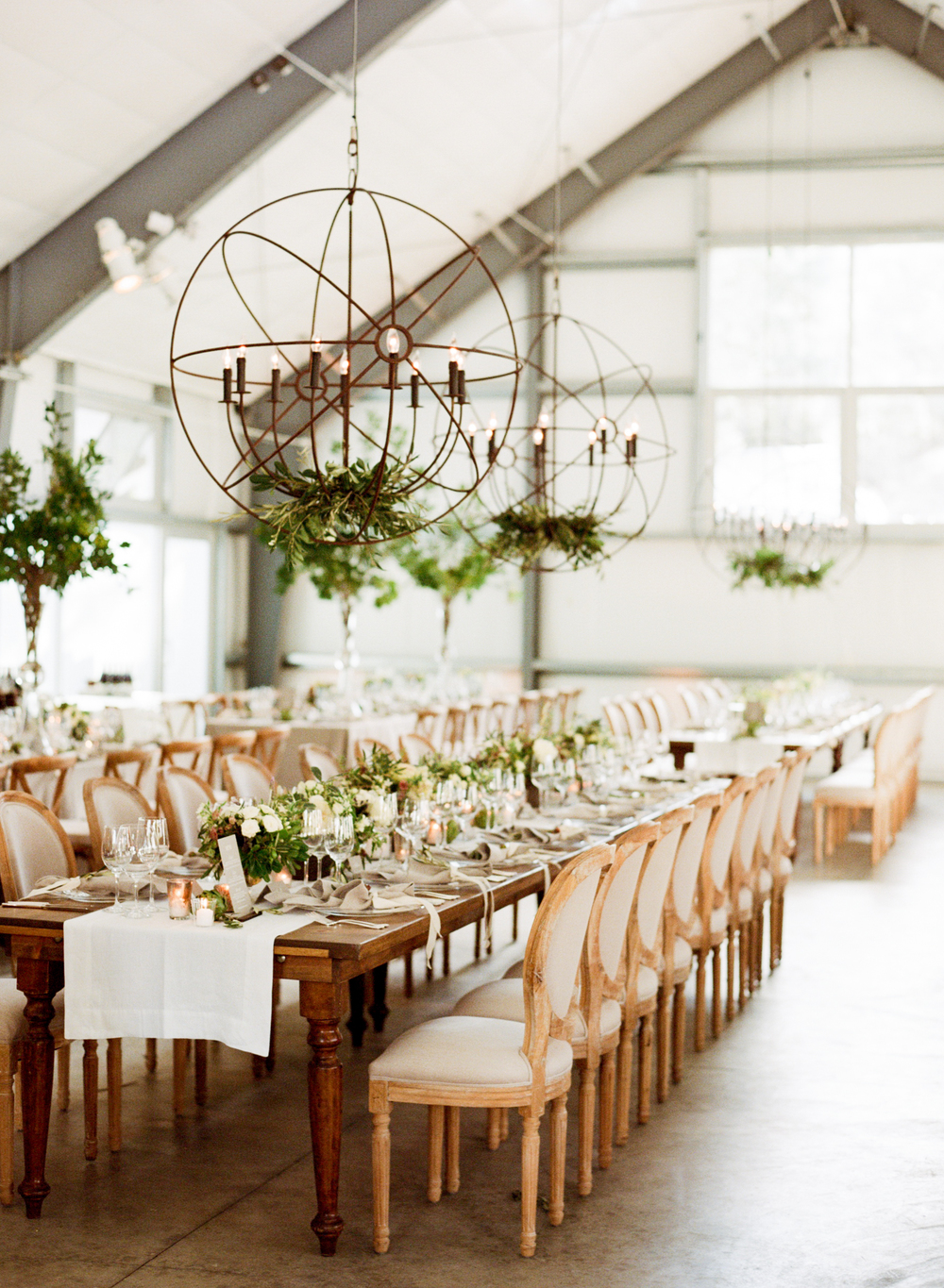 Cast iron sphere chandeliers hang in airy barn reception;  Sylvie Gil Photography