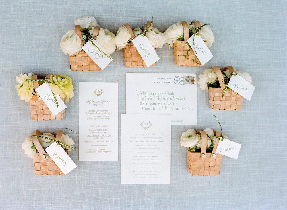 Wedding favors for the bridal party arranged around an elegantly calligraphied invitation suite; photo by Sylvie Gil