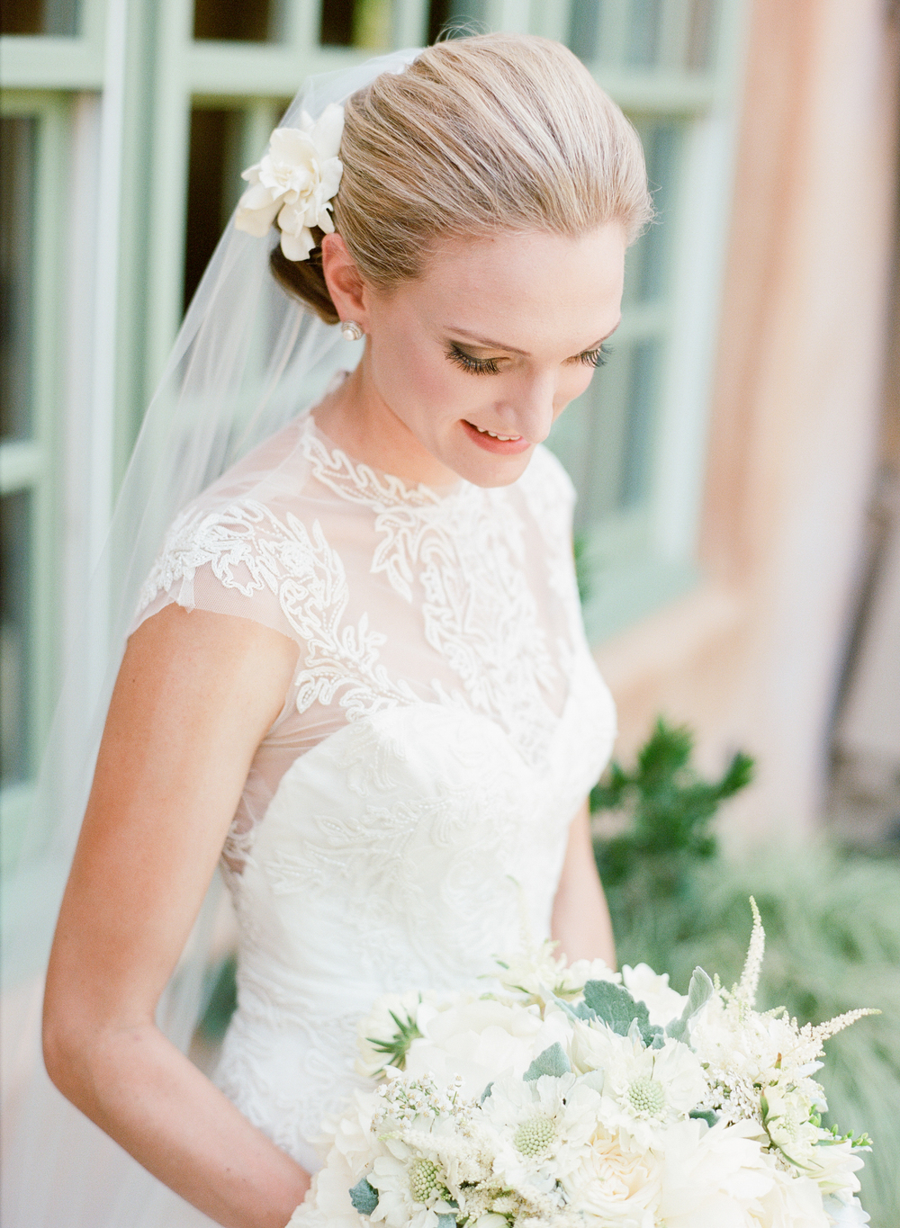 A glowing classic bride gazes at her white bouquet before the ceremony; photo by Sylvie GIl