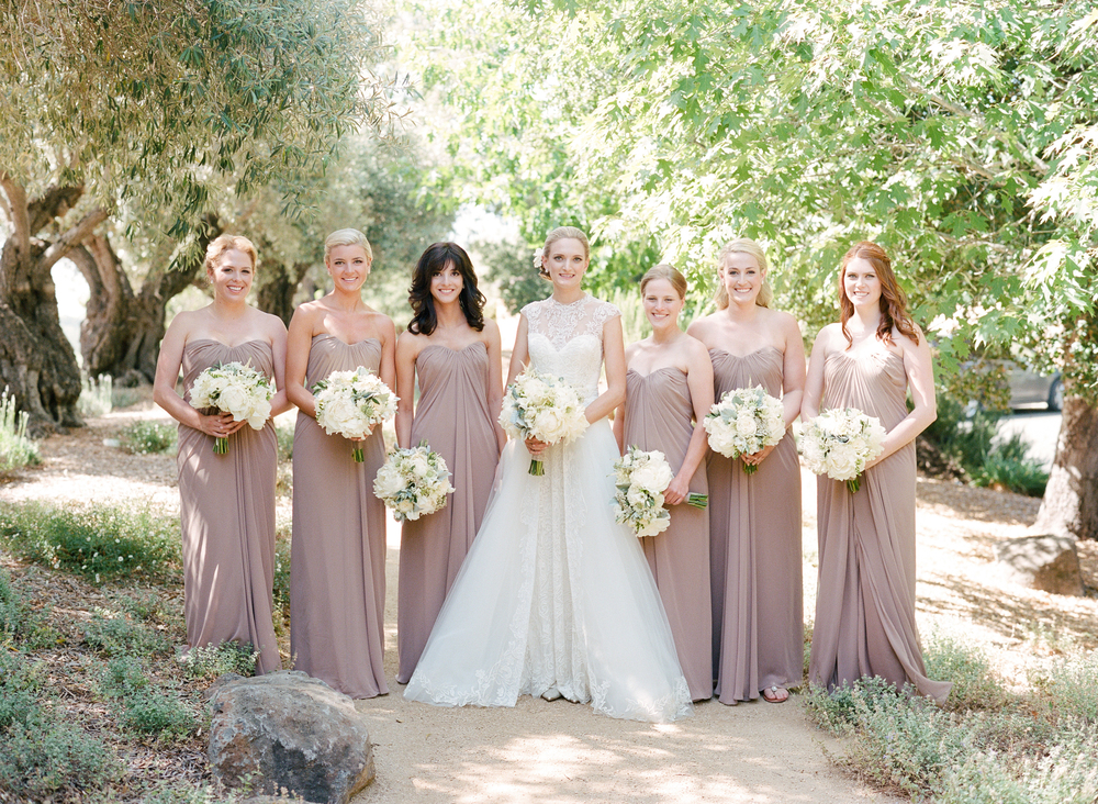 Six bridesmaids and the bride, holding classic white bouquets of roses and peonies; photo by Sylvie Gil