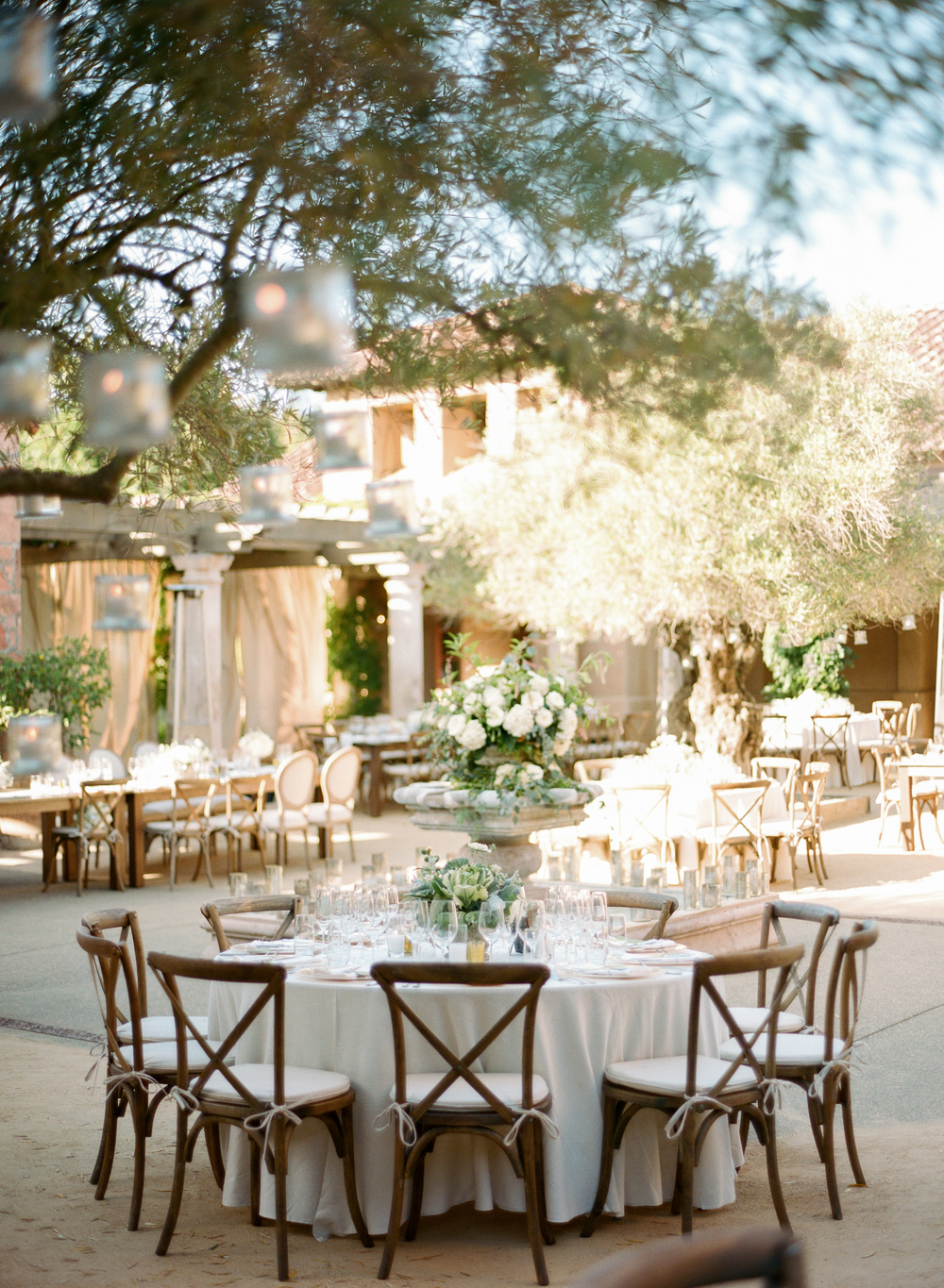 Votive candles hang from olive branches in the courtyard, a fountain sits in the center of the elegantly arranged reception tables; photo by Sylvie Gil