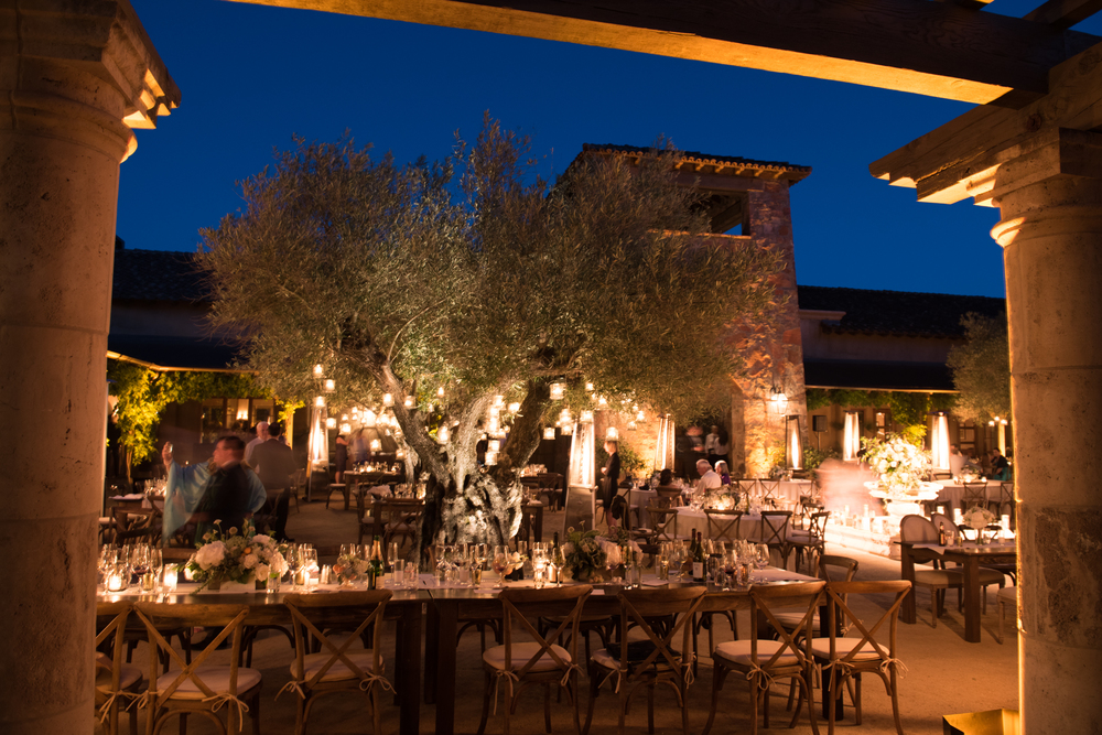 The nightlit reception space, candles glow in the trees as the sky darkens over the outdoor olive tree courtyard; photo by Sylvie Gil