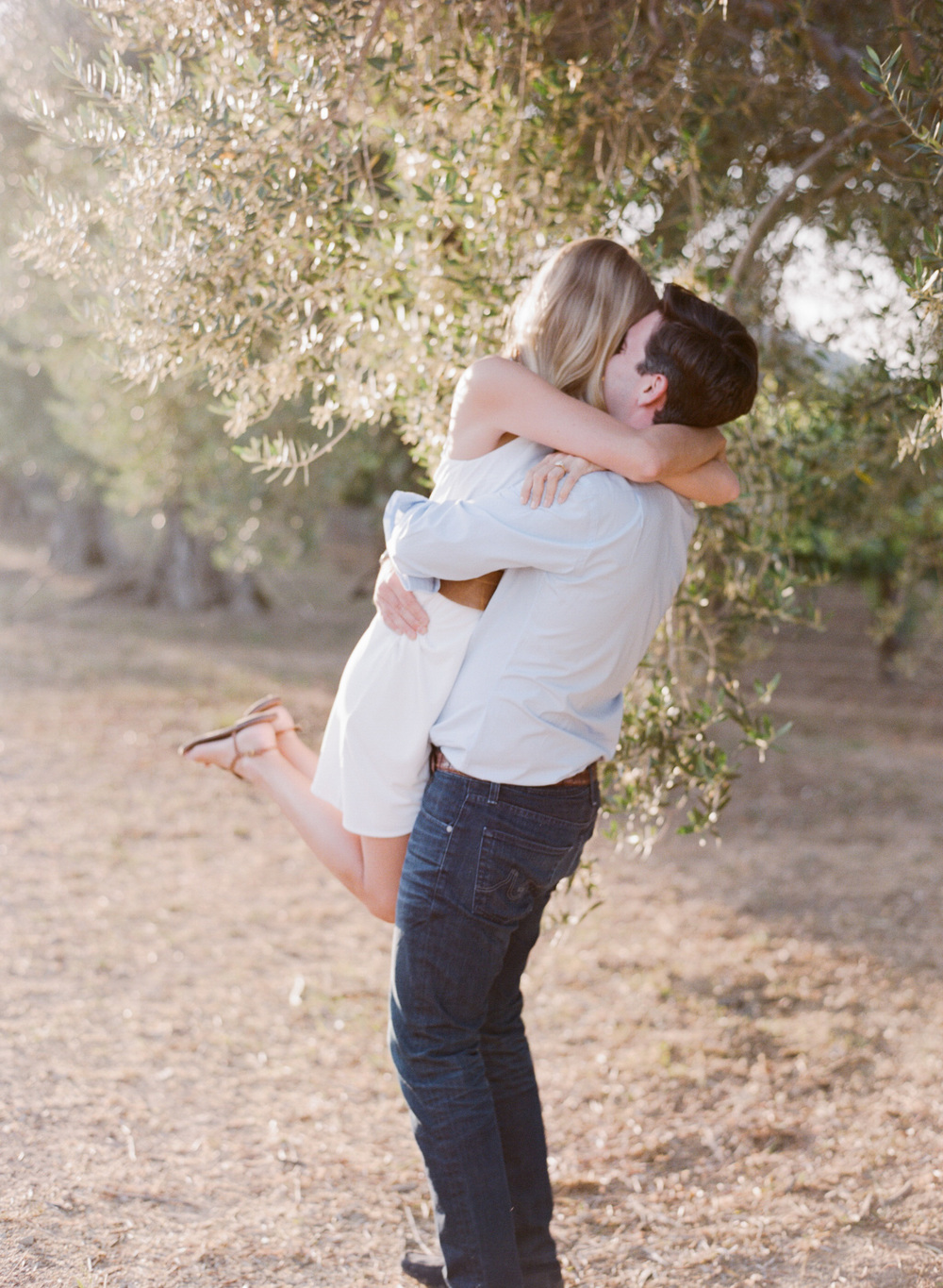 A bride-to-be jumps into her fiancee's arms in a Napa Valley vineyard  during an engagement session with Sylvie Gil.